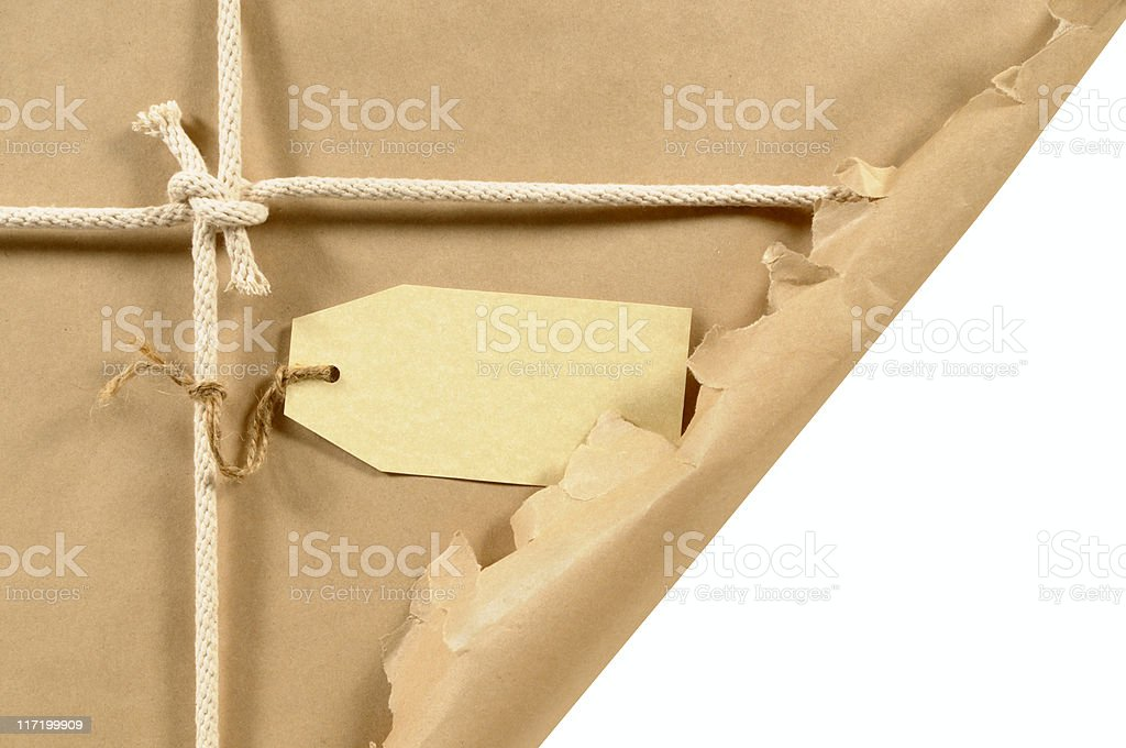 Torn brown parcel with tag royalty-free stock photo