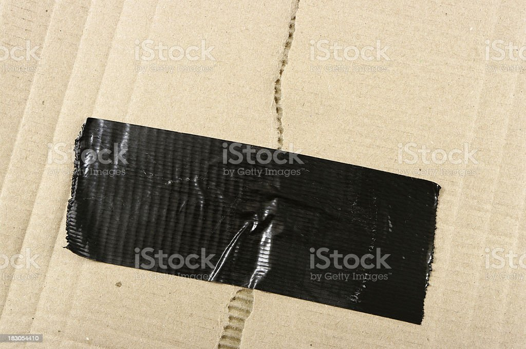 Torn Corrugated Cardboard Background With Duct Tape Repair royalty-free stock photo