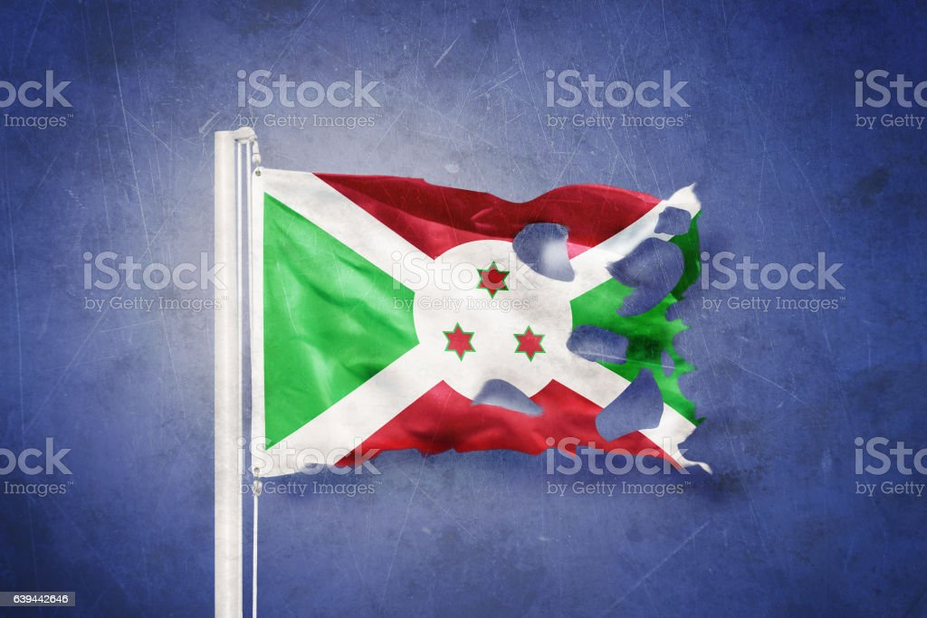 Torn flag of Burundi flying against grunge background stock photo