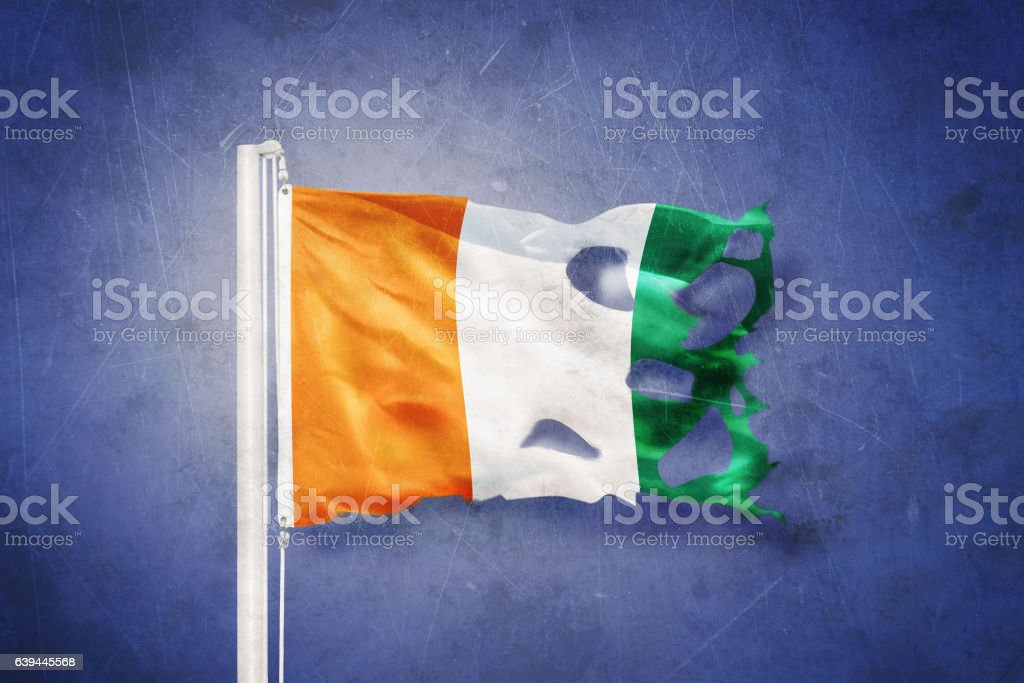 Torn flag of Cote d'Ivoire flying against grunge background stock photo