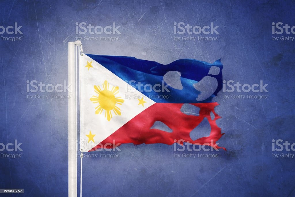 Torn flag of Philippines flying against grunge background stock photo