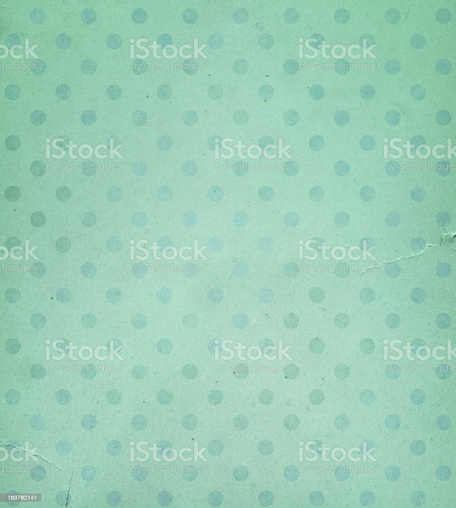 torn green paper with faded dots stock photo