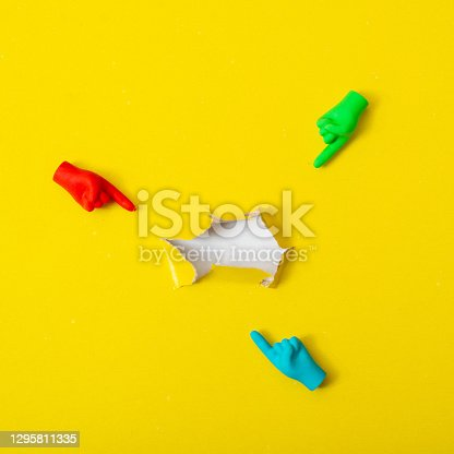 istock Torn hole in the paper. Multi-colored hands point to her. 1295811335