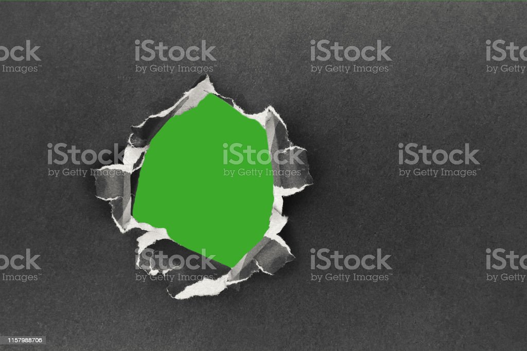 Torn hole in the sheet of paper on a green background. Rip and torn...
