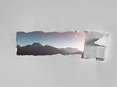 istock Torn hole in the white paper with a picturesque view of mountains. Creative concept of seeing the world, traveling, open your mind 1129638477