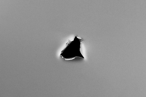Hole on metal plate. Clean metal background with hole, shot in studio with macro lens.