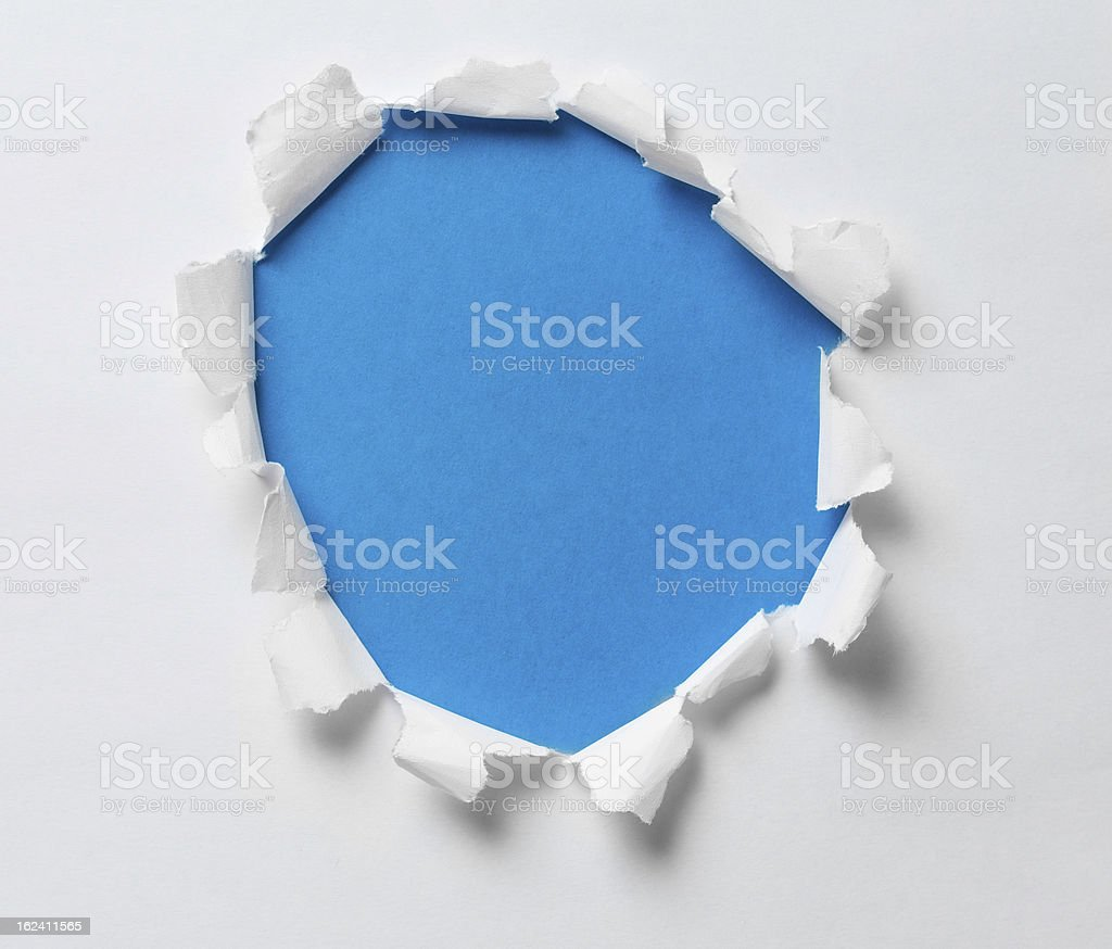 torn hole on the paper with blue background royalty-free stock photo