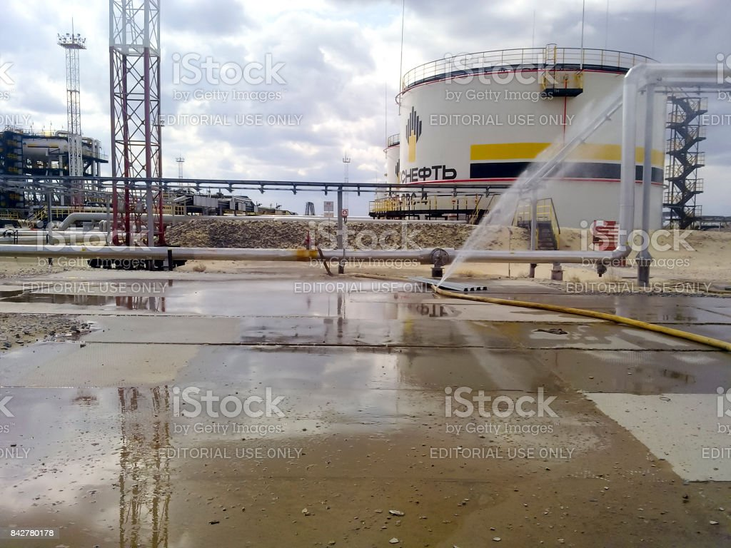 Torn hose of the fire hose. Water filled concrete pavement. Oil reservoir and pipelines. Equipment oil fields of Western Siberia stock photo