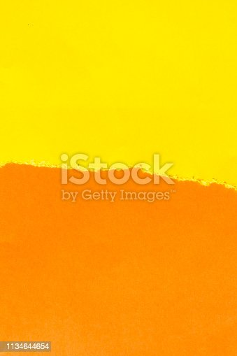 istock Torn off piece of yellow paper on an orange background. 1134644654