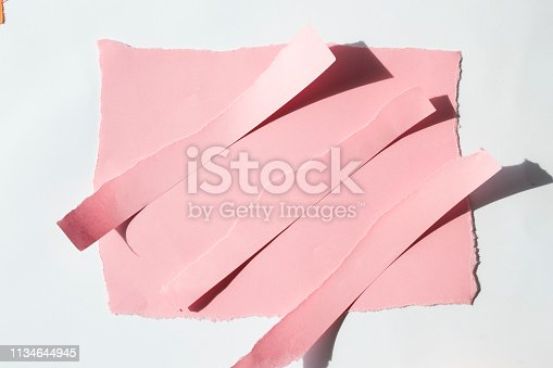 istock Torn off scraps of pink paper on a white background. 1134644945