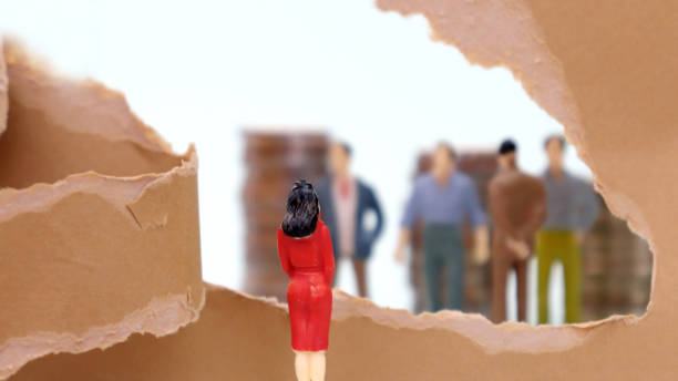 Torn paper and miniature people. Discriminatory view of women in the company. Torn paper and miniature people. Discriminatory view of women in the company. discriminatory stock pictures, royalty-free photos & images