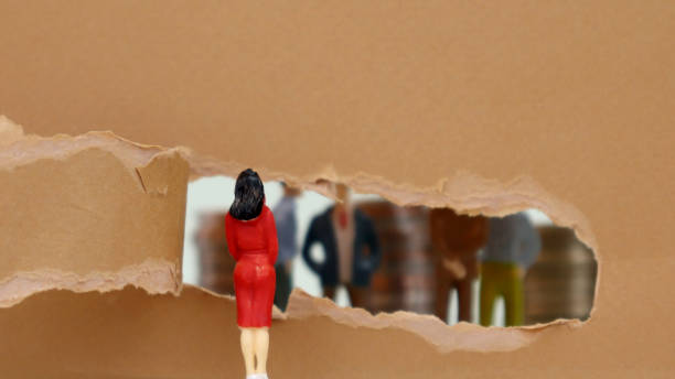 Torn paper and miniature people. The concept of gender inequality in the field of society. Torn paper and miniature people. The concept of gender inequality in the field of society. discriminatory stock pictures, royalty-free photos & images