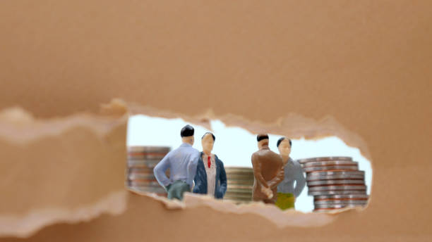 Torn paper and miniature people. The concept of working men. Torn paper and miniature people. The concept of working men. discriminatory stock pictures, royalty-free photos & images
