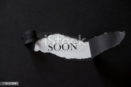 843847560 istock photo Torn paper box with word coming soon in low light 1194428061