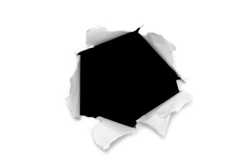 Torn paper hole over black background.