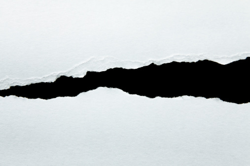 Torn grey paper over a black background. Space for copy