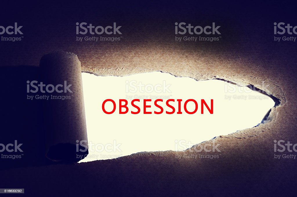 Torn paper with light focused on word 'obsession'. stock photo