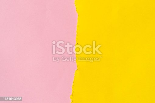 istock Torn piece of yellow paper on a pink background. 1134643958
