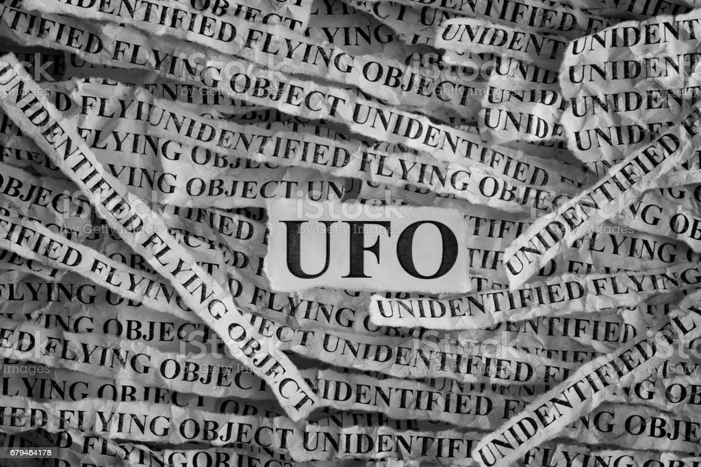 Torn pieces of paper with abbreviation UFO. Unidentified flying object royalty-free stock photo