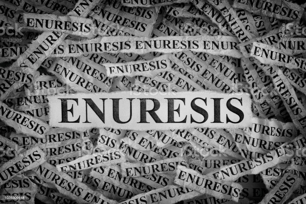 Torn pieces of paper with the words Enuresis stock photo