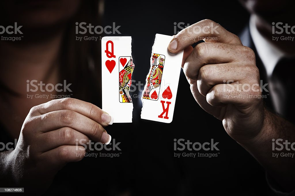 Torn playing cards symbolize divorce stock photo