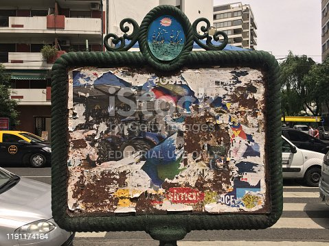 Buenos Aires, Argentina - November 30, 2019: Lots of broken posters glued one over the other on city billboard used for advertising purposes. This are a city classic and are distributed all over it