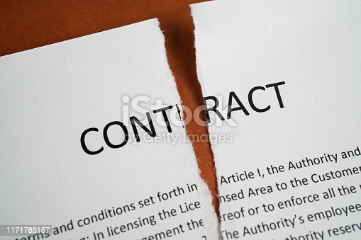 Close up of torn up contract on a wooden desk