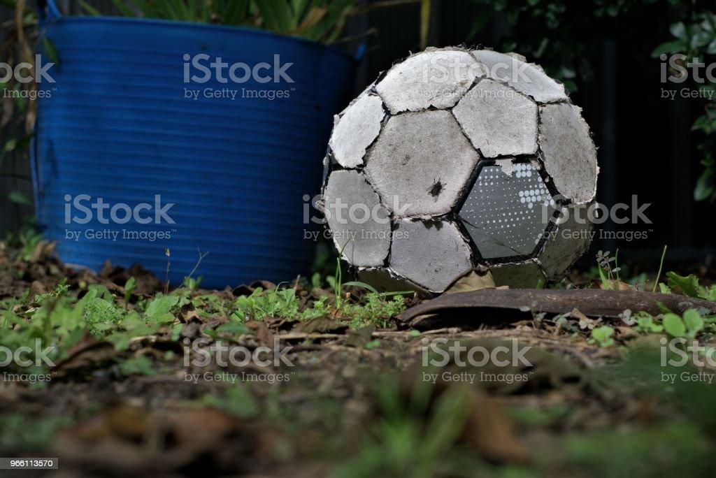 Rivs upp gamla fotboll bollen låg på gräs. Slitna fotboll som värdelösa objekt. - Royaltyfri Abstrakt Bildbanksbilder
