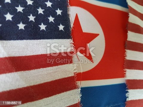A torn flag of the USA and behind it, a North Korean flag. I did not actually tear this flag, that would violate the US flag code! I found it on the street!