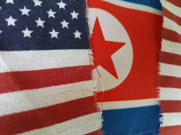 Torn US flag with North Korea background A torn flag of the USA and behind it, a North Korean flag. I did not actually tear this flag, that would violate the US flag code! I found it on the street! shock tactics stock pictures, royalty-free photos & images