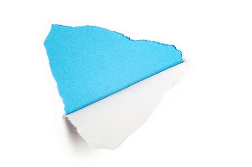 Torn white paper revealing light blue background