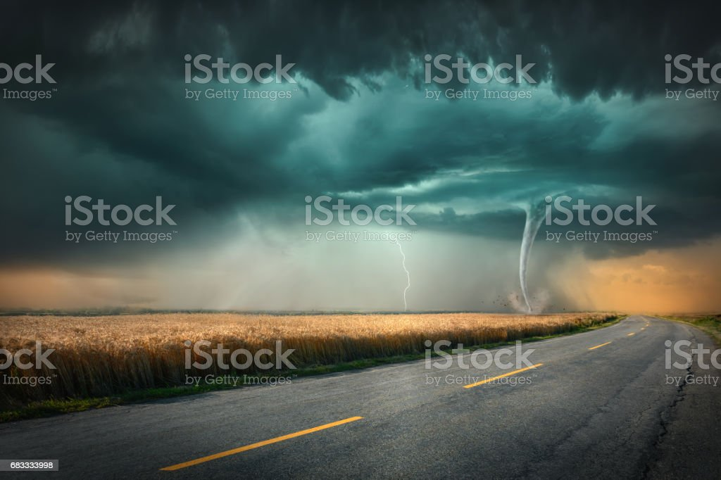 Tornado and thunder storm on agricultural meadow at sunset stock photo