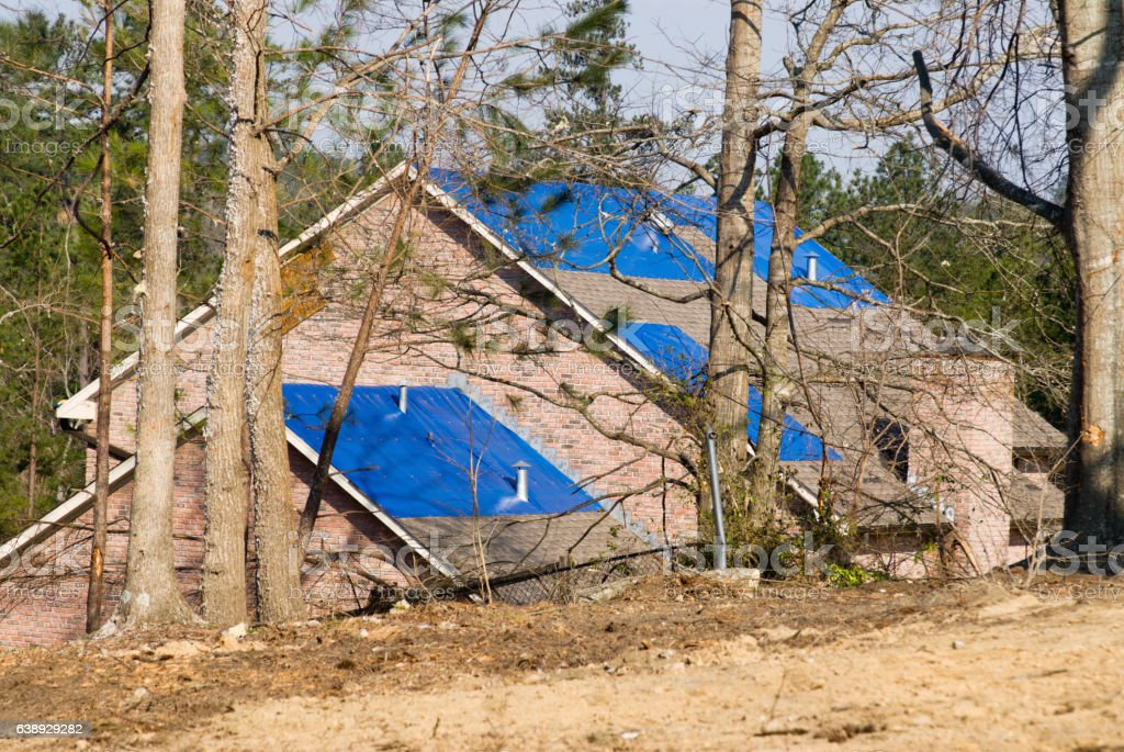 tornado damaged house with a blue tarpaulin on the roof stock photo