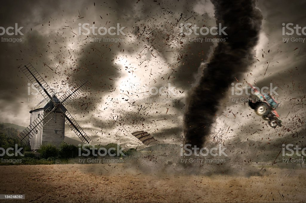 Tornado hurls tractor across field with windmill on horizon royalty-free stock photo