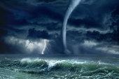 Nature force background - huge tornado, bright lightning in dark stormy sky, stormy sea, big waves
