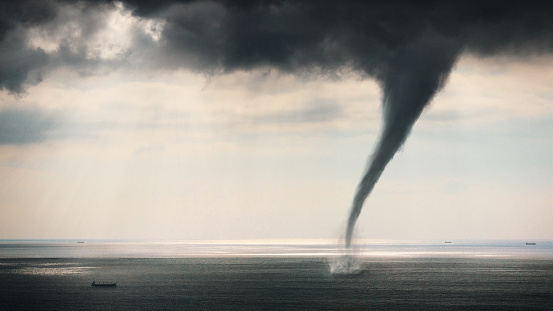 Tornado Sea view horizontal image with cargo ship near tornado. Nature power concept. Climate change. Weather illustration. Adventure travel conceptual photography.