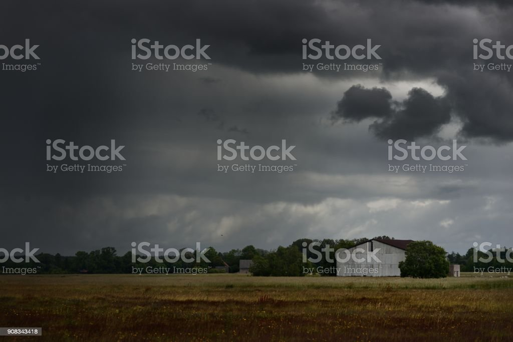 Tornado storm clouds above the shed in the countryside stock photo