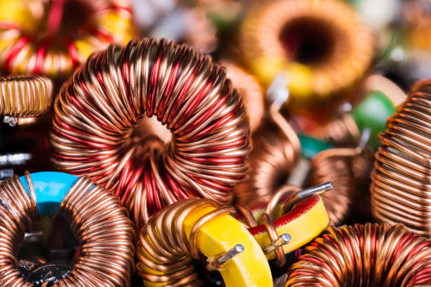 Toroidal electronic inductors on heap in an electrotechnical background stock photo