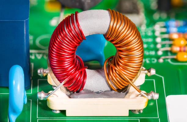Toroidal transformer coil detail in holder. Colorful wire winding on inductor with ferrite core stock photo