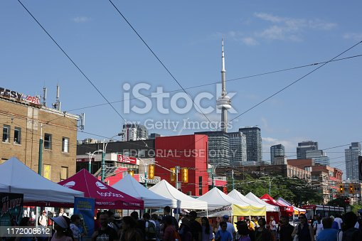 Toronto, Canada - August 17, 2019: Festival attendees visit rows of tents at the 2019 Toronto Chinatown Festival on Spadina Avenue at Dundas Street West. The CN Tower and upscale condo towers are in the background.