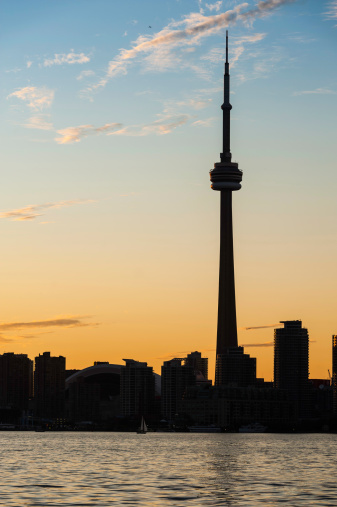 Toronto, Canada - 10th September 2011: The landmark spire of the CN Tower illuminated above the iconic cityscape of skyscrapers and high rise condominiums of downtown Toronto, Canada, reflecting in Lake Ontario under vibrant sunset skies.