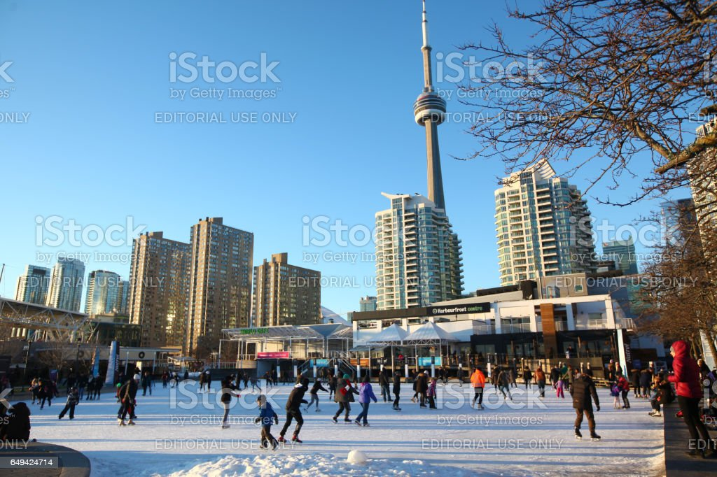 Toronto Harbourfront Skating Rink Toronto, Ontario, Canada - January 4, 2017: People skating on the skating rink in Toronto Harbourfront with downtown Toronto buildings and CN Tower in the background. Winter leisure time in downtown Toronto. Toronto activities in winter CN Tower Stock Photo