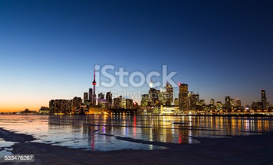 The Toronto Skyline in the Winter from the East at sunset showing the frozen lake and patches of snow on the ice