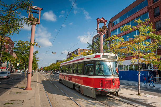 toronto tram rolling through chinatown in summer canada - toronto streetcar stock photos and pictures