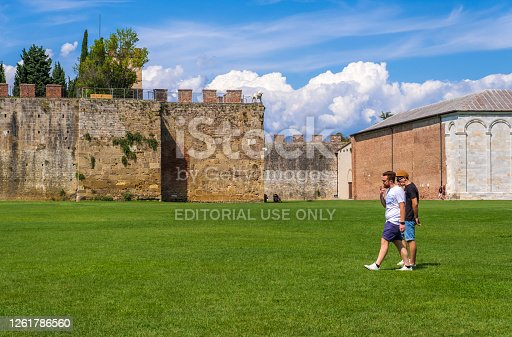 Pisa, Italy - August 14, 2019: Tourists walking on the background of the Le mura di Pisa. These were the walls of the city of Pisa, now they surround the historic center of the city