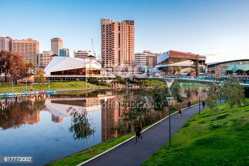 Adelaide, Australia - September 11, 2016: Torrens river bank with people walking through foot bridge in Adelaide city centre at sunset