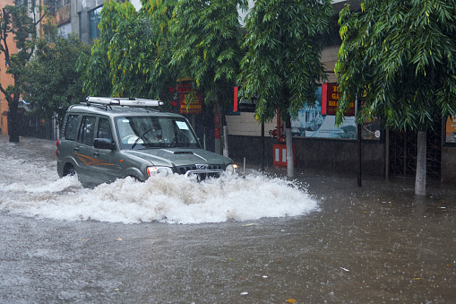 A public car moving through flooded street, caused by overnight monsoon rain which have flooded several parts of city, causing havoc in everyday life. More rains are in forecast across this week.