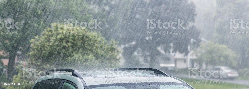 Drenched cars parked in residential home driveways during a...