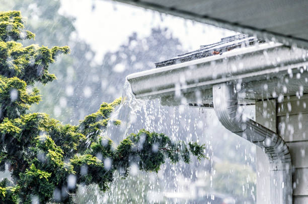 Torrential Summer Rain Storm Water Overflowing Roof Gutters stock photo