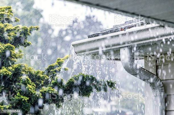 Photo of Torrential Summer Rain Storm Water Overflowing Roof Gutters